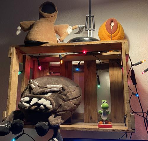 Ein Bild von einer zum Regal umfunktionierten Obstkiste auf und in der verschiedene Plüschtiere sitzen: Kenny aus Southpark, der Tod aus Nichtlustig. Zecki, das 1.April-FC-St.-Pauli-Maskottchen und Yoshi aus dem Mario-Universum.
